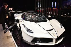 """© Licensed to London News Pictures. 14/11/2017. London, UK.  A visitor views a LaFerrari Aperta, 2017. Preview of """"Ferrari: Under the Skin"""", an exhibition at the Design Museum to mark the 70th anniversary of Ferrari.  Over GBP140m worth of Ferraris are on display from private collections including Michael Schumacher's 2000 F1 winning car.  The exhibition runs 15 November to 15 April 2018.  Photo credit: Stephen Chung/LNP"""