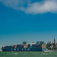 A heavily loaded container ship sails towards the Bay Bridge in San Francisco Bay, California.