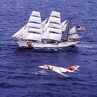 Aerial view of the US Coast Guard's Falcon Jet flying by the USS Eagle, a Barque Tall ship used for training.