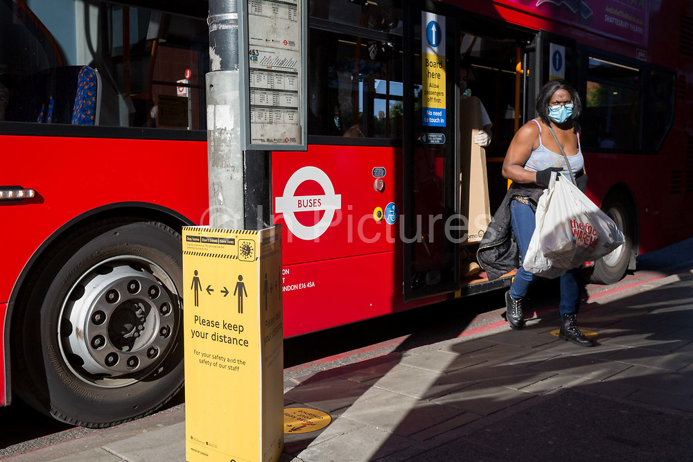 As the number of new Coronavirus cases in the UK climbs to 201,101, with UK deaths now standing at 30,076 - the highest recorded in Europe, passengers exit a bus next to a Transport For London TFL sign asking the public to maintain safe social distances while travelling on the capitals public transport during the continuing Covid lockdown, on 6th May 2020, in south London, England. Front doors on London buses are now disabled to avoid exposure of drivers to the virus, plus no fares are being taken on journeys to further avoid card reader contact.