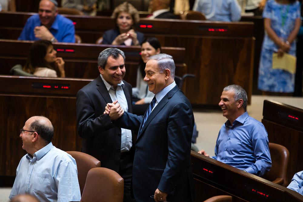 Israeli Prime Minister Benjamin Netanyahu (Center, R) shakes hands with Israeli lawmaker, Knesset Member Zeev Elkin at the Knesset, Israel's parliament in Jerusalem, on May 18, 2015