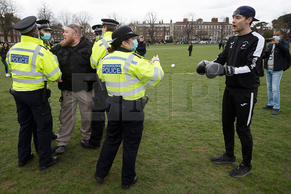 © Licensed to London News Pictures. 06/03/2021. London, UK. A protester is rested by police officers at an anti-vaccination and anti-lockdown demonstration organised by Jam For Freedom in Richmond. The group is using music to create positive effects and health against the current tier regulations and anti-vaccination for the Covid-19 disease. Photo credit: Ray Tang/LNP