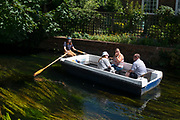 A rower wearing a face shield takes socially distanced visitors along a peaceful stretch of the river Stour during their boat tour of Canterbury during the Coronavirus pandemic, on 18th July 2020,  in Canterbury, Kent, England.