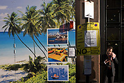 A man adjusts his mp3 player with the hoarding of a travel business's construction site showing a tropical beach paradise and images of world cities with a No Parking sign. A confusing and incongruous scene of the Urban and the Paradise are seen together on this London street as people emerge from their office and make calls or plays with mobile devices. The palm trees on the beach and the images of world cities such as Sydney, New York and Hong Kong make it a landscape of global travel, a shrinking world of intercontinental jet setting. Added to that is the temporary traffic sign telling Londoners not to park at this location between specific dates.