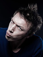 studio portrait on black background of a funny expressive caucasian man pucker strain
