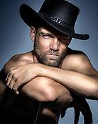 Portrait sexy d'un cowboy avec son chapeau.