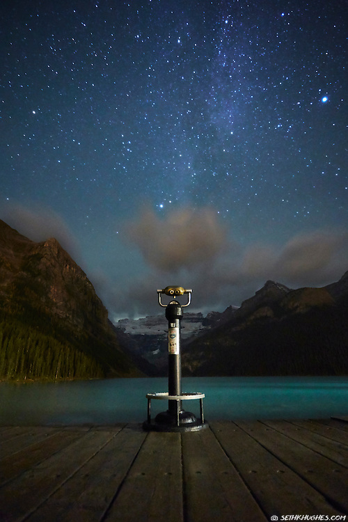 A telescope in the foreground looking up at the Milky Way galaxy in a star-filled night sky.
