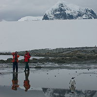 Tourists explore a cove at Damoy Point on Wiencke Island, Antarctica. Behind is Mount Luigi, highest of  the Seven Sisters of Fief in the Fief Mountains.