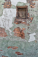 Brick wall revealed beneath several layers of green and white surface material.  This is view of the building from an alley in Hudson, New York.