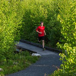 A young man trail running on the summit of Mount Agamenticus in York, Maine.