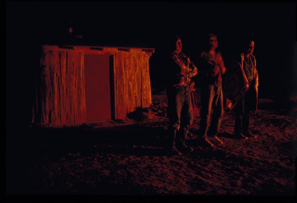 Medicine man Sam Begay, Thomas Keams and Paul Keams outside the ceremonial hogan at night during the Balckening Way.