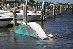 October 8, 2016 - St. Augustine Beach, Florida, U.S. - WILL VRAGOVIC   |   Times.A Fish and Wildlife Conservation officer takes photographs of damage as an overturned boat floats between slips at the Conch House Marina Resort after Hurricane Matthew tore through the area in St. Augustine Beach, Fla. on Saturday, Oct. 8, 2016. (Credit Image: © Will Vragovic/Tampa Bay Times via ZUMA Wire)