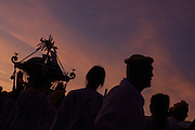 Mikoshi and supporters in silhouette  during the Hamaorisai Matsuri that takes place on Southern Beach in Chigasaki, near Tokyo, Kanagawa, Japan Monday July 18th 2011. The festivals marks the celebration of Marine Day and the rescuing of a divine image that was washed ashore in the area. Over thirty Mikoshi or portable shrines are carried through the night from surrounding shrines to arrive on the beach for sunrise. There they are blessed and then carried into the surf to purify them.