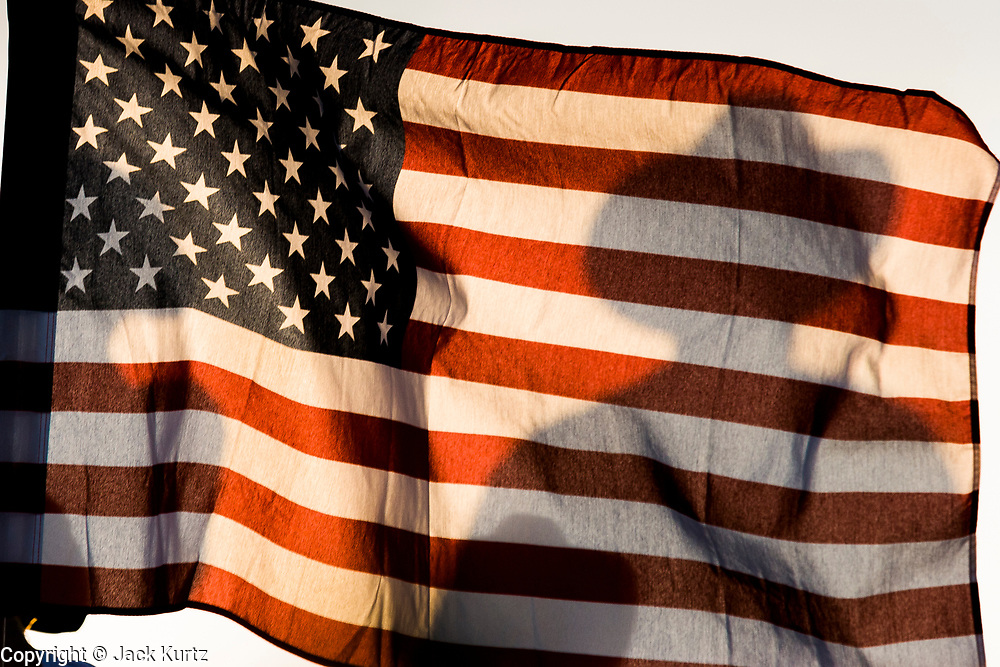 16 APRIL 2005 - NACO, AZ: A Minuteman volunteer, standing behind an American flag, watches the US/Mexico border near Naco, AZ. The Minuteman Project is a volunteer effort to deter illegal immigrants from entering the US without documentation. The Minuteman volunteers call the Border Patrol when they see undocumented immigrants entering the US. Organizers claim to have thousands of volunteers signing up for the effort and they claim to reduced illegal immigration through their area by almost 100 percent and are preparing plans to extend their program to Texas, New Mexico and California. PHOTO BY JACK KURTZ