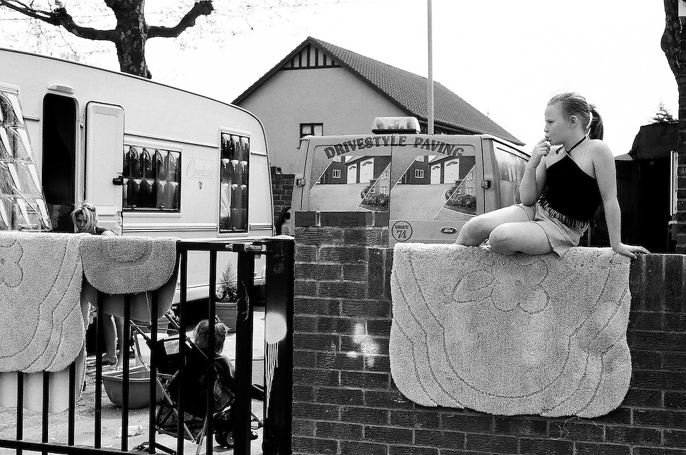 Irish Traveller girl sunbathing on her family's pitch wall on the South Bermondsey Council-owned Travellers' site, London.