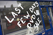 The words 'Last few days DVD Sale' are painted on a window of a closed business in Kennington South London.