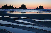 Pools of water reflect the sunset and the sea stacks of Point of the Arches at Shi Shi Beach, Olympic National Park, Washington.
