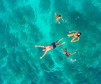 Aerial view of family of 4 swimming in turquoise Adriatic sea, Sutivan, Croatia.
