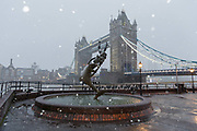 The Girl with a Dolphin Fountain is seen in front of Tower Bridge during a heavy snow shower on December 10th, 2017. Much of the UK has been hit by heavy snow and The Met Office have issued a yellow weather warning for snow and ice across most of the United Kingdom.
