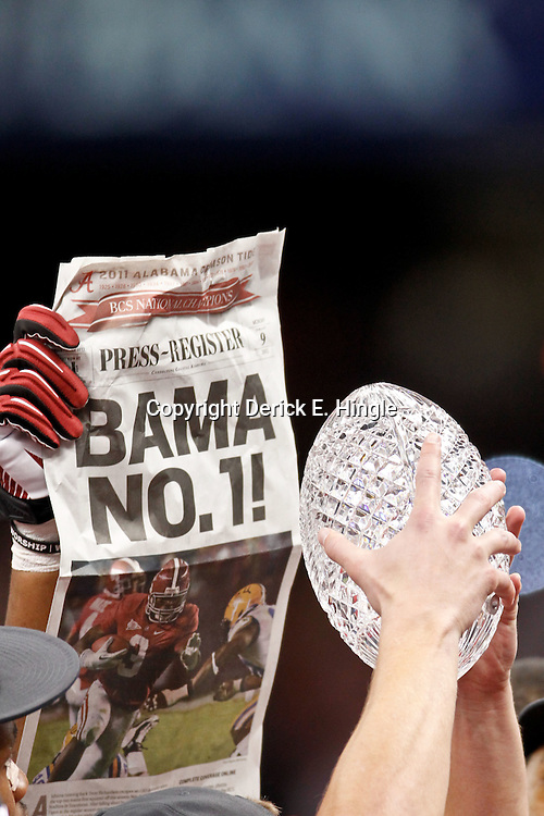 Jan 9, 2012; New Orleans, LA, USA; A Alabama Crimson Tide players raises  The Coaches Trophy crystal football in celebration after the 2012 BCS National Championship game win over the LSU Tigers at the Mercedes-Benz Superdome.  Mandatory Credit: Derick E. Hingle-US PRESSWIRE