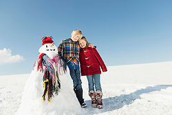 Girl and boy with snowman, smiling, Bavaria, Germany