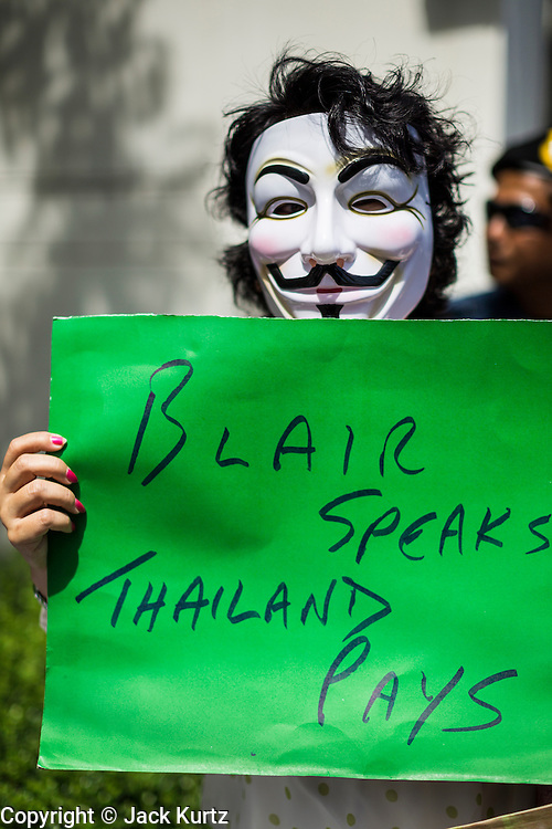 """27 AUGUST 2013 - BANGKOK, THAILAND: A Thai """"White Mask"""" protester holds up a sign protesting against the fee allegedly paid to Tony Blair to bring him to speak in Thailand. About 25 people, including at least two British citizens, picketed the British embassy in Bangkok Tuesday morning. They were protesting against former British Prime Minister Tony Blair, who is expected to speak to a political reform commission established by Thai Prime Minister Yingluck Shinawatra. The protest leaders were invited in to the Embassy grounds to speak to representative of the British government. The protest disbanded afterwards. No one was arrested during the protest, which lasted a little over an hour. The Thai government has denied paying Blair his usual fee of about $800,000 (US).        PHOTO BY JACK KURTZ"""