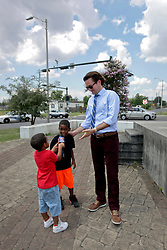 29 August 2015. Lower 9th Ward, New Orleans, Louisiana.<br /> Hurricane Katrina 10th Anniversary.<br /> WDSU's Travers Mackel finds himself a couple of young apprentices at the monument dedicated to the victims and survivors of the storm. <br /> Photo credit©; Charlie Varley/varleypix.com.