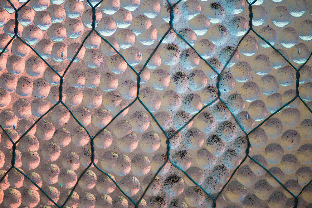 Macro photo of chicken wire against dimpled glass