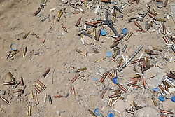 © Licensed to London News Pictures. 30/06/2014. Khanaqin, UK Khanaqin, Iraq. Cigarette butts, water bottle lids and empty rifle and machine gun cartridges litter the ground at a Kurdish peshmerga base in Jalawla, Iraq. Counted by Kurds as part of their homeland, fighting in the town of Jalawla now consists of occasional skirmishes and exchanges of fire between snipers and heavy machine guns on both sides.<br /> <br /> The peshmerga, roughly translated as those who fight, is at present engaged in fighting ISIS all along the borders of the relatively safe semi-automatous province of Iraqi-Kurdistan. Though a well organised and experienced fighting force they are currently facing ISIS insurgents armed with superior armament taken from the Iraqi Army after they retreated on several fronts. Photo credit : Matt Cetti-Roberts/LNP