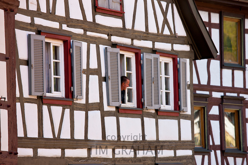 Man at window of traditional quaint timber-framed house in Schiltach in the Bavarian Alps, Germany