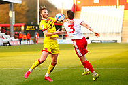 Ben Coker of Stevenage is grabbed by a Walsall player during the EFL Sky Bet League 2 match between Stevenage and Walsall at the Lamex Stadium, Stevenage, England on 20 February 2021.