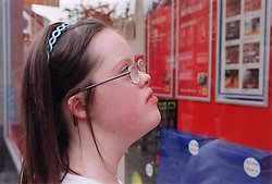 Portrait of teenage girl with Downs Syndrome reading notices in shop window,