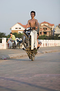 Two young barechested vietnamese men have fun with their bike and make some wheeling. Hanoi, Vietnam, Asia