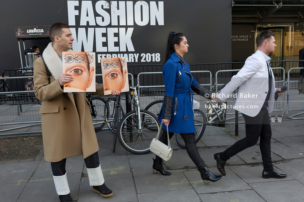 Free magazines featuring a model's eye on the cover are being handed out on the first day of London Fashion Week, in the Strand, on 16th february 2018, in London, England,