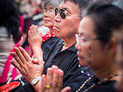 12 OCTOBER 2104 - BANG BUA THONG, NONTHABURI, THAILAND: People pray for Apiwan Wiriyachai during the first day of his funeral rites at Wat Bang Phai in Bang Bua Thong, a Bangkok suburb, Sunday. Apiwan was a prominent Red Shirt leader, member of the Pheu Thai Party of former Prime Minister Yingluck Shinawatra, and a member of the Thai parliament. The military government that deposed the elected government in May, 2014, charged Apiwan with Lese Majeste for allegedly insulting the Thai Monarchy. Rather than face the charges, Apiwan fled Thailand to the Philippines. He died of a lung infection in the Philippines on Oct. 6. The military government gave his family permission to bring him back to Thailand for the funeral. He will be cremated later in October. The first day of the funeral rites Sunday drew tens of thousands of Red Shirts and their supporters, in the first Red Shirt gathering since the coup.    PHOTO BY JACK KURTZ