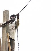 CAPTION: Putting up electricity cables, part of a SPEED mini grid in Baharayen. LOCATION: Baharayen, Faizabad District, Uttar Pradesh, India. INDIVIDUAL(S) PHOTOGRAPHED: Ram Teerath.