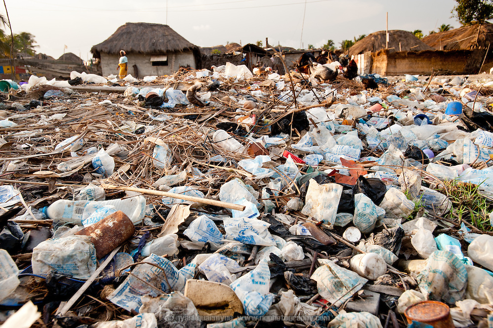 Forced to move to low-lying land as the traditional site of their village is being washed away, villagers in Azizanya are using their garbage as landfill in a desperate attempt to reclaim swampland for settlement.