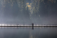 Two walkers take in the view on the floating bridge at Sasamat Lake in Port Moody, British Columbia, Canada.  White Pine Beach (popular during the summer months) is just around the corner from here and along with Sasamat Lake is within Belcarra Regional Park.