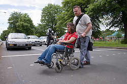 Young woman with cerebral palsy in a wheelchair with her boyfriend crossing the road,