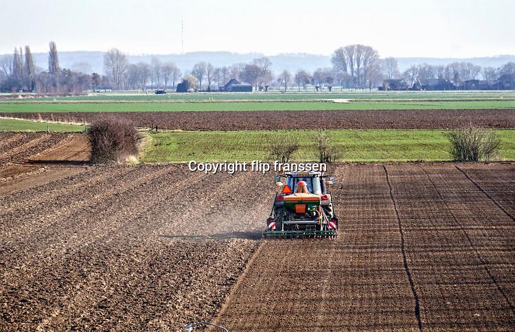 Neder;and, Kekerdom, 27-2-2019Een boer, loonwerker, rijdt met een tractor, trekker, over een akker, het land, om kunstmest op te brengen . Het is vloeibaar en wordt met injectoren in de grond gebracht .Foto: Flip Franssen