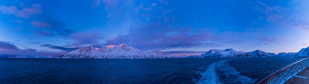 A panorama of alpenglow at sunset on the coastal peaks in Norway, from the ms Trollfjord ship on the southbound voyage. <br /> <br /> This is a 7-section panorama, handheld, with the 15mm Venus Optics lens and Sony a7III, stitched with ACR.