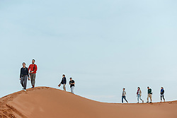 Silhouettes of hikers on sand dunes, Erg Chebbi, Saharan Desert, Morocco