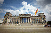 The Reichstag building with puffy clouds in Berlin, Germany.