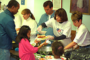 Volunteers serving family at Sharing and Caring Hands soup kitchen.  Minneapolis Minnesota USA