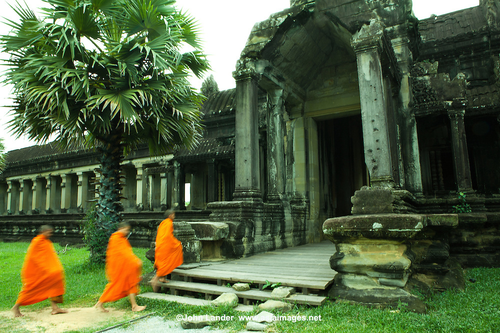 """Angkor Wat Monks - Angkor was built for the king Suryavarman II in the early 12th century as his state temple and capital city. As the best preserved temple at Angkor Archeological Park, it is the only one to have remained a significant religious centre since its foundation - first Hindu dedicated to the god Vishnu, then Buddhist. It is the world's largest religious building. The temple is admired for the grandeur and harmony of the architecture, its extensive bas-reliefs, and for the numerous guardian spirits adorning its walls. The modern name, Angkor Wat, means """"City Temple""""; Angkor which comes from the Sanskrit word meaning capital or city. Wat is the Khmer word for temple. Prior to this time the temple was known as Preah Pisnulok, after the posthumous title of its founder, Suryavarman II."""