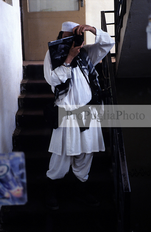 Self portrait of a photographer wearing local dress and a copy of the Kashmir's book.