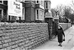 Elderly woman walking past residential home