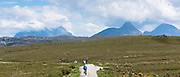 Tourists cycling by Stac Pollaidh - Stack Polly - in glacier mountain range in the North West Highlands Geopark in Coigach region of Scottish Highlands