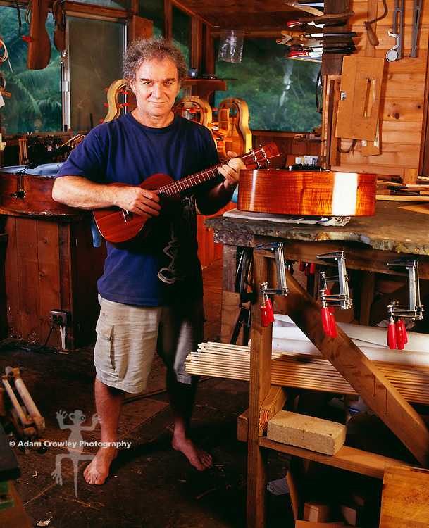 Luthier (Mature man) playing guitar in his workshop, portrait