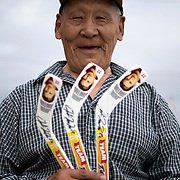 Jordin Tootoo grew up in a small village along the Hudson Bay only a hundred miles from the Arctic Circle. The first Inuit to play professionally in the National Hockey League, Tootoo is close to his family and friends to nearly everyone in Rankins Inlet in Northeast Canada. This man walks purchased three souvenir hockey sticks with Jordin's picture on them at a local market. <br /> <br /> Image available for licensing and for a personal print. Please Add To Cart and select the size and finish. All prints are delivered directly to you from the printer.